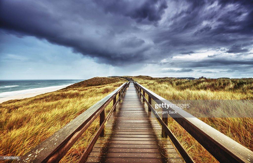 Autumn on Sylt - Wooden path under dramatic sky : Stock Photo