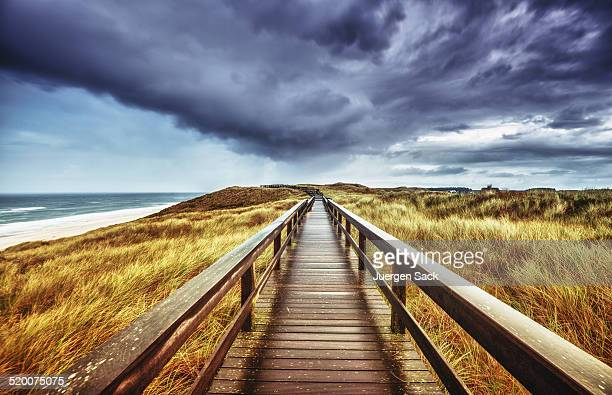 Autumn on Sylt - Wooden path under dramatic sky