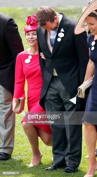Autumn Phillips curtsies and Peter Phillips bows his head as Queen Elizabeth II passes by in her horse drawn carriage on day 5 of Royal Ascot at...
