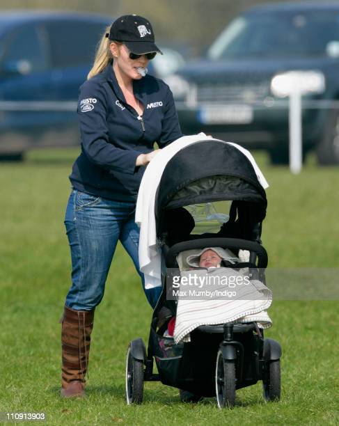 Autumn Phillips holds a dummy in her mouth as she pushes daughter Savannah Phillips in her pushchair at the Gatcombe Park Horse Trials on March 26...