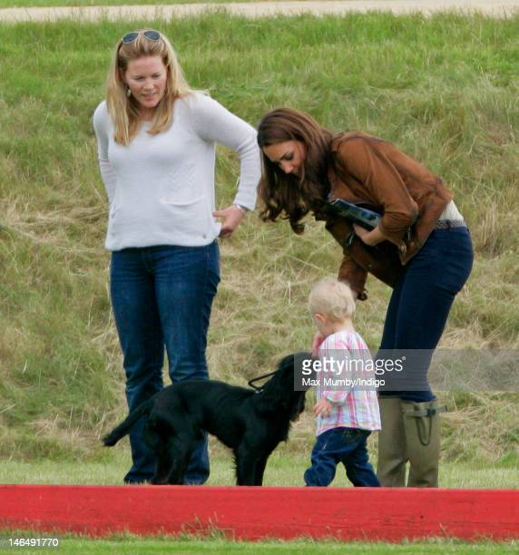 Autumn Phillips looks on as Catherine Duchess of Cambridge and Savannah Phillips play with Lupo the dog at The Golden Metropolitan Polo Club Charity...