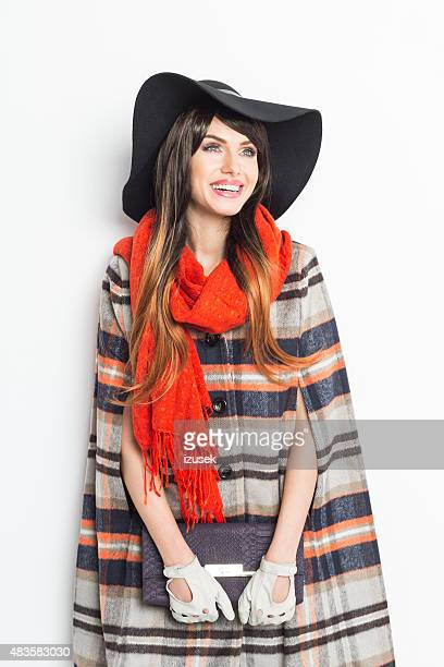 Autumn portrait of fashionable young woman wearing poncho and hat