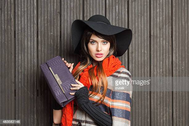 autumn portrait of fashionable young woman wearing poncho and hat - long purse stock photos and pictures