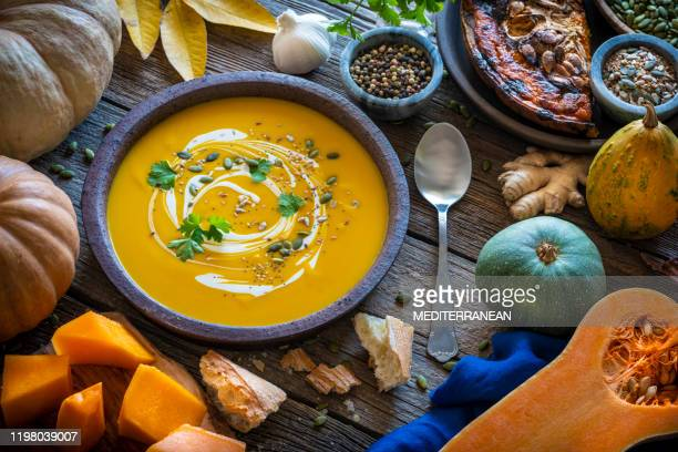 autumn pumpkin soup and ingredients on wood - liscio foto e immagini stock