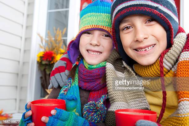 autumn- sibling drinking hot chocolate - mitten stock photos and pictures