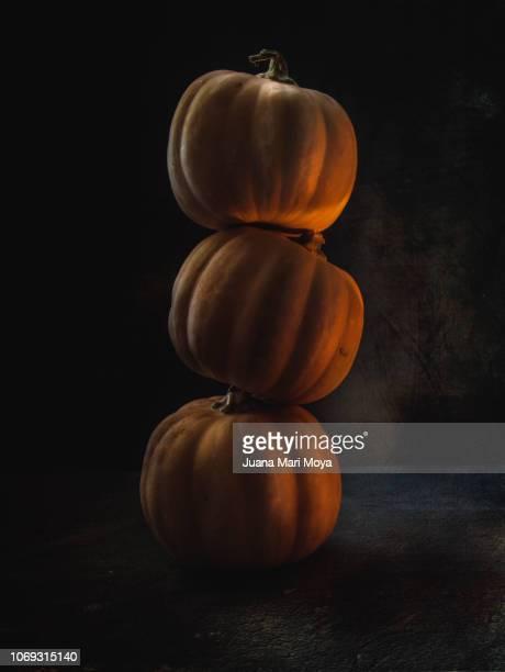 Autumn still life, of three pumpkins on dark background with warm light