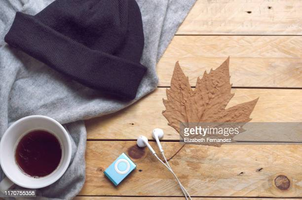 autumn still life with tea cup, scarf, knit hat, audio equipment, earbuds and dry leaf. cozy concept. - brown hat stock pictures, royalty-free photos & images