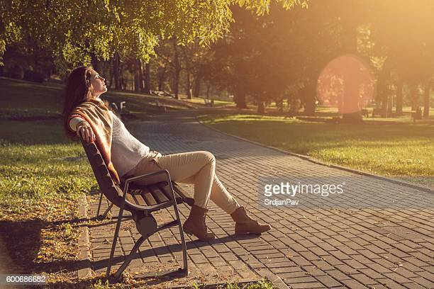 autumn sunbathing - park bench stock pictures, royalty-free photos & images