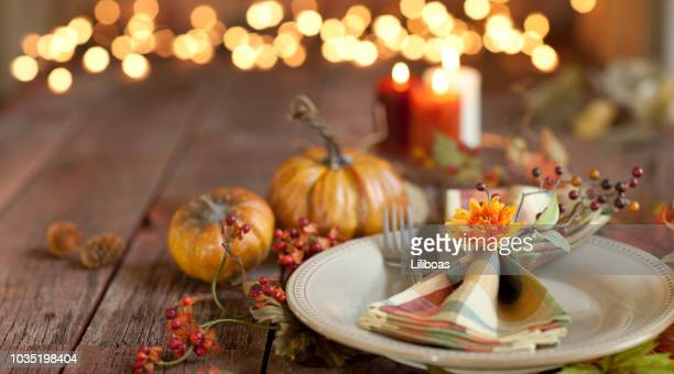 Autumn Thanksgiving dining table place setting on an old wood rustic table