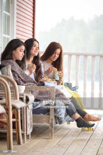 autumn weekend, sisters having tea and cookies on cabin deck - hygge stock pictures, royalty-free photos & images
