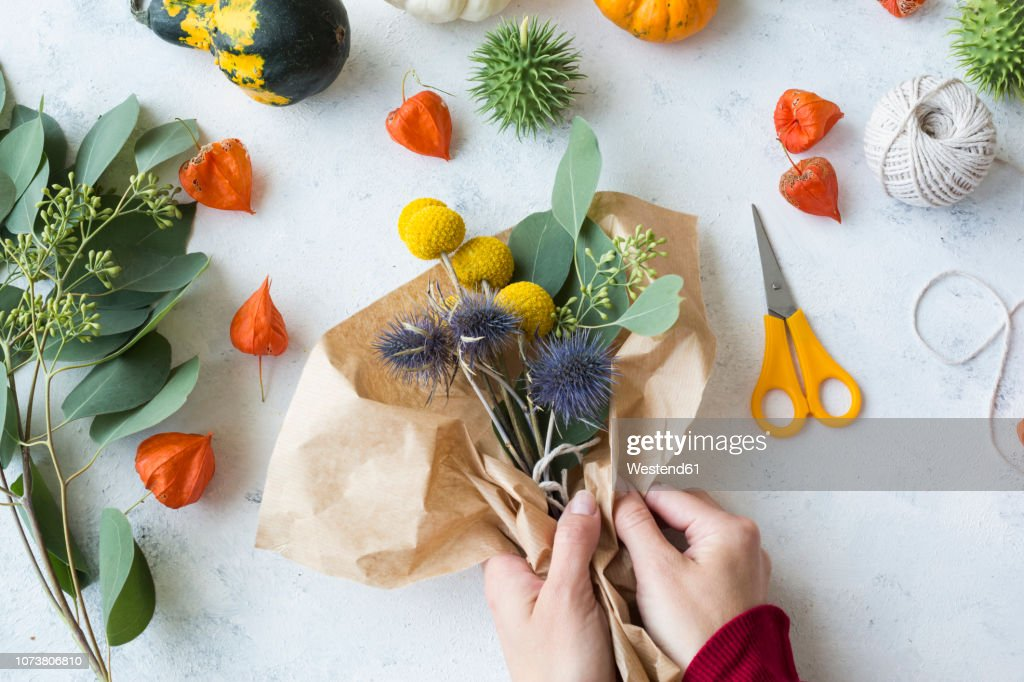 Autumnal decoration, ornamental pumpkins, hands wrapping bunch of flowers : Stock Photo