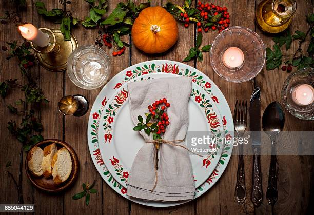 Autumnal laid table with pumpkin, holly and candle light