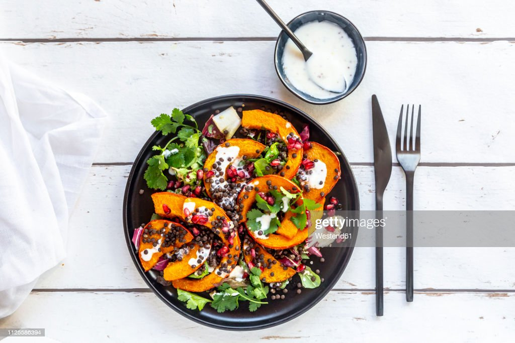 Autumnal salad with fried pumpkin, lentils, radicchio, pomegranate seeds, leaf salad and parsley with dressing : Stock Photo
