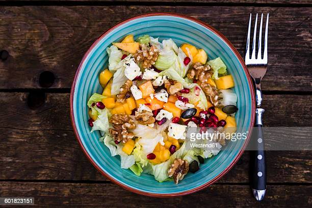 Autumnal salad with kaki, feta cheese, iceberg lettuce, pumpkin seeds, pomegranate and walnuts