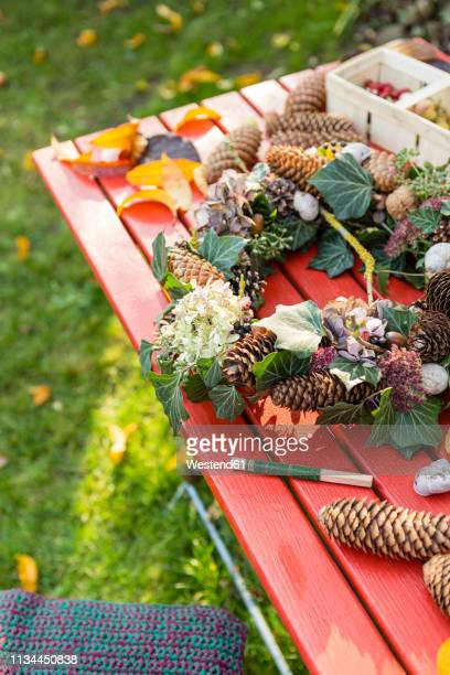 autumnal wreath with hortensia, pine cones and ivy on garden table - art and craft stock pictures, royalty-free photos & images