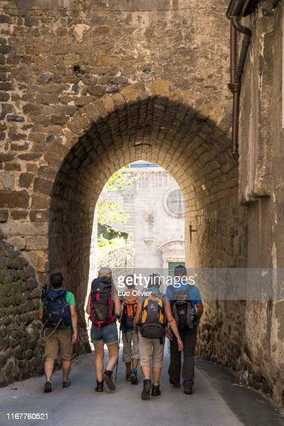 auvergne - haute-loire - saint james way - hikers in the streets of puy-en-velay. - le puy stock pictures, royalty-free photos & images