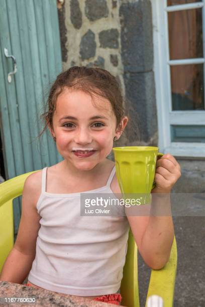 auvergne - rhone-alpes - haute-loire - family trip to the farm. a little girl happily drinks some milk. - auvergne rhône alpes stock pictures, royalty-free photos & images