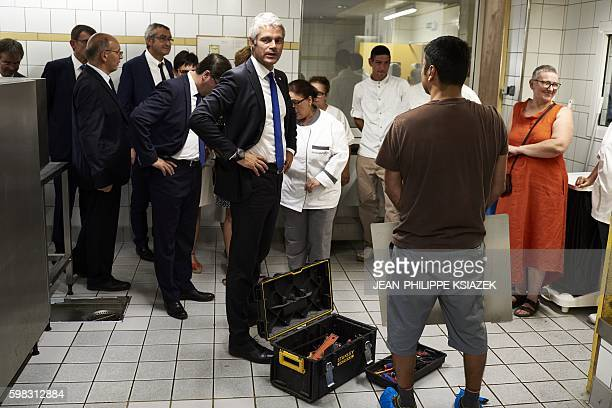 AuvergneRhoneAlpes region chairperson Laurent Wauquiez talks with workers at the 'Galilee' highschool on September 1 in Vienne where the securing...