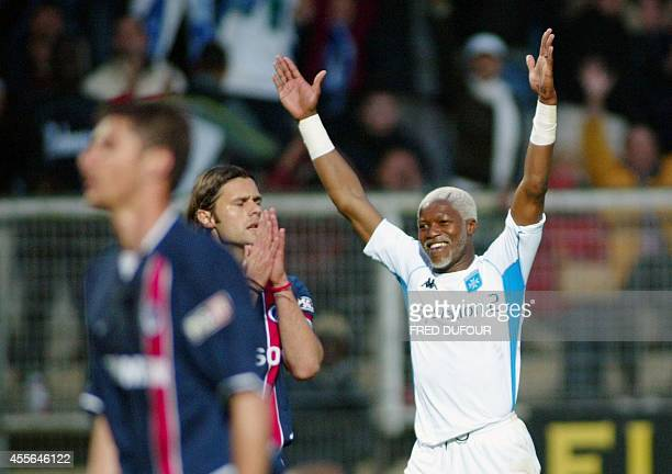 Auxerre forward Dijbril Cisse jubilates after scoring next to Paris defender Argentinian Mauricio Pochettino during their French league soccer match...
