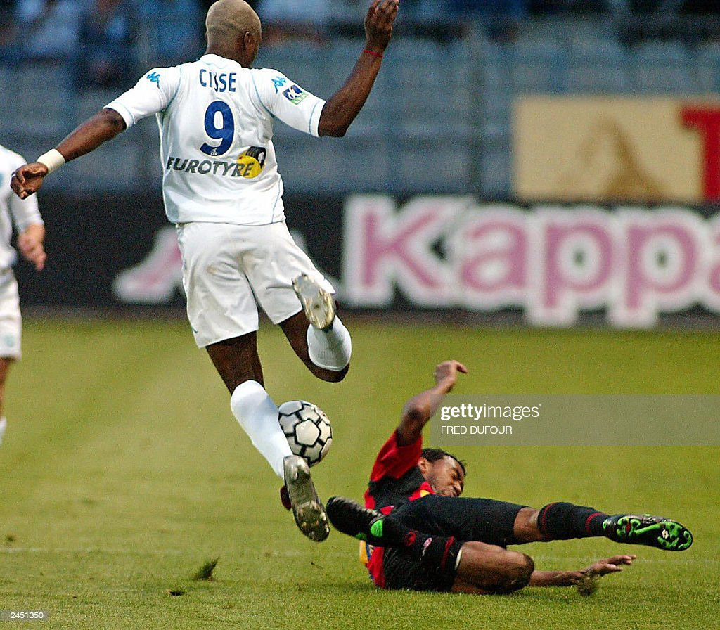 Auxerre's forward Djibril Cisse is tackle by Rennes' Brazilian ...