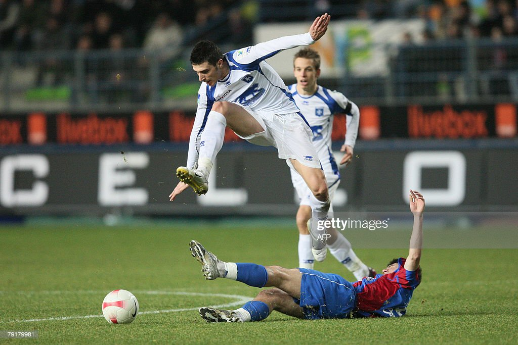Auxerre's George Niculae (L) jumps over Caen's Gregory Proment (R) during the French L1 football match Caen vs. Auxerre, 23 January 2008 at the Michel d'Ornano stadiumin in Caen, western France.