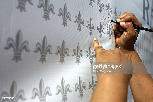 Ava Conerly signs a wall of Fleur De Lis in remberance of her father Fred Conerly Sr who died during Hurricane Katrina during the Ringing of the...
