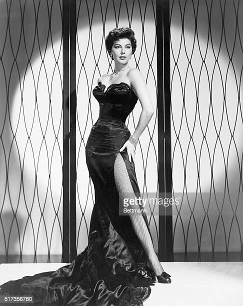 1952 Ava Gardner actress Full length movie publicity still Photo shows actress in long black satin strapless gown with long slit showing fishnet...