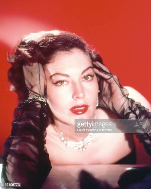 Ava Gardner US actress poses with her hands wearing chiffon gloves either side of her head in a studio portrait against a red background circa 1960