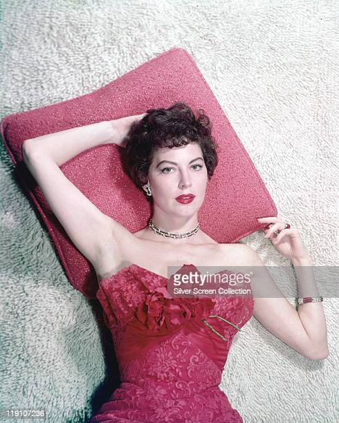 Ava Gardner US actress reclining with her head on a red pillow wearing a red shoulderless dress in a studio portrait circa 1960