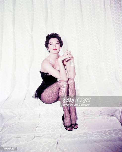 Ava Gardner , US actress, wearing a black bodice and fishnet tights in a studio portrait, against a white background, circa 1955.