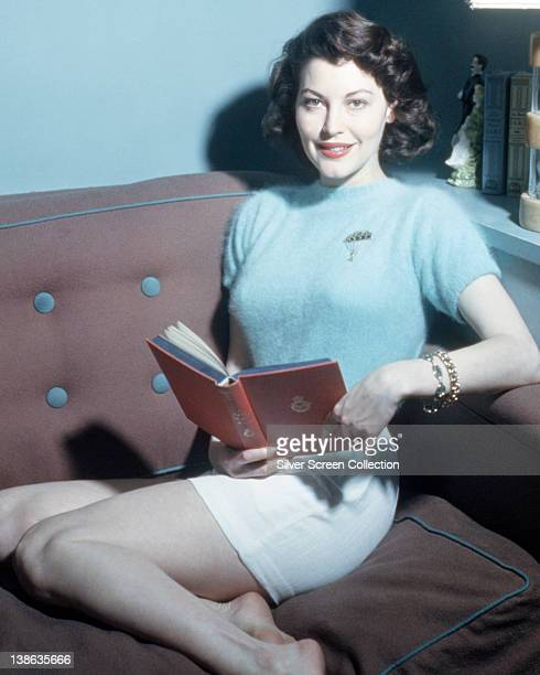 Ava Gardner US actress wearing a light blue short sleeve jumper while reading a book as she reclines on a sofa circa 1950