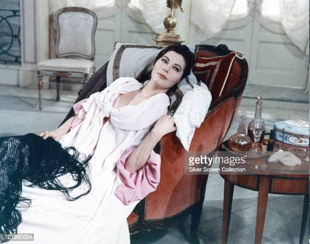 Ava Gardner US actress wearing a white dress as she reclines in an armchair a small table beside the armchair features two decanters and a glass on a...
