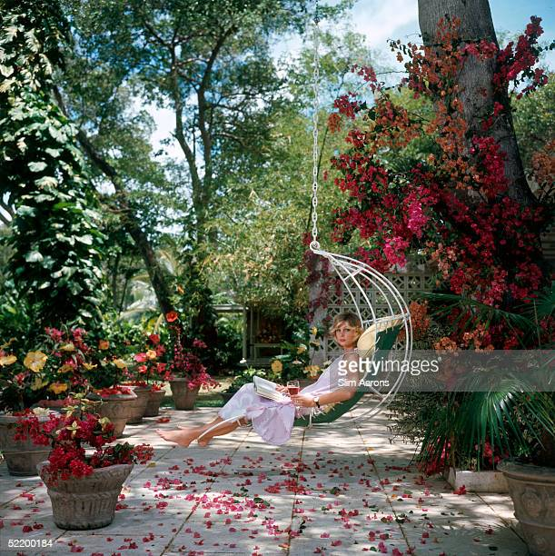 Ava Marshall relaxes with a book amongst the bougainvillea in Barbados April 1976