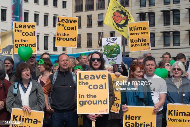 Avaaz activists hold up signs that read 'Leave the coal in the ground' and 'Klimavorreiter Kohleausstieg' during a rally at the Brandenburg Gate on...