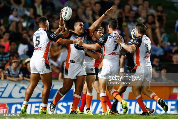 Avagalu Seumanufagai of the Tigers celebrates with team mates after scoring a try during the round six NRL match between the North Queensland Cowboys...