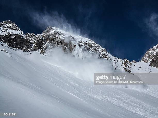 Avalanche cascading down snowy slope