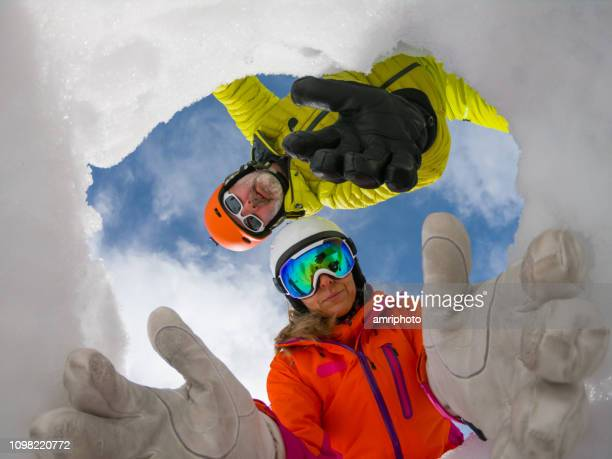 avalanche mountain rescue team reaching out helping hands in snow hole to save victim - rescue worker stock pictures, royalty-free photos & images