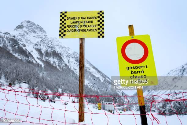 Avalanche warning boards are on display at a closed area in the small resort of Zinal Swiss Alps on January 9 after the access road cut by heavy...