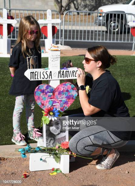 Avalynn Briggs of Washington looks on as her mother Nichole Briggs writes a note on a cross set up for shooting victim Melissa Ramirez on October 1...