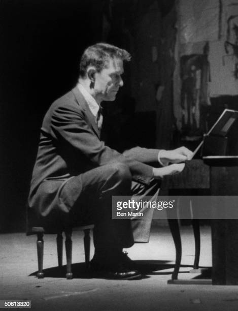 Avantgarde minimalist composer John Cage playing a children's size piano