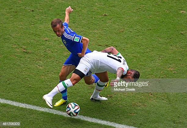 Avdija Vrsajevic of Bosnia and Herzegovina and Ashkan Dejagah of Iran compete for the ball during the 2014 FIFA World Cup Brazil Group F match...