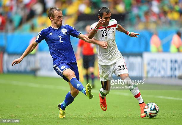 Avdija Vrsajevic of Bosnia and Herzegovina and Mehrdad Pooladi of Iran compete for the ball during the 2014 FIFA World Cup Brazil Group F match...