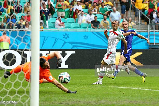 Avdija Vrsajevic of Bosnia and Herzegovina shoots and scores his team's third goal past goalkeeper Alireza Haghighi of Iran during the 2014 FIFA...