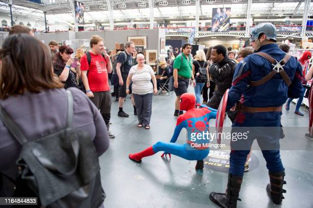 Avengers cosplayers in character as Sipder Man Black Panther and Captain America posse for photographs with the public during London Film and Comic...