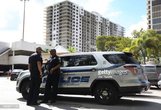 Aventura City police officers stand across the street from the condo building that has a possible connection to alleged bomber Cesar Sayoc and his...