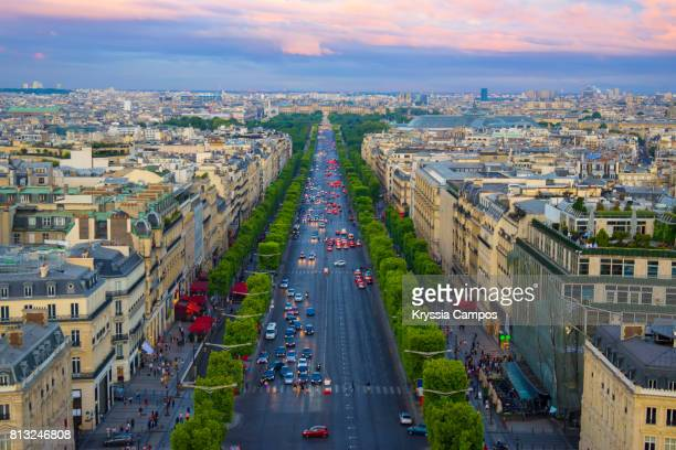 avenue des champs elysees in paris at sunset - champs elysees quarter stock pictures, royalty-free photos & images