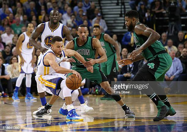 Avery Bradley and Amir Johnson of the Boston Celtics try to steal the ball from Stephen Curry of the Golden State Warriors at ORACLE Arena on April 1...