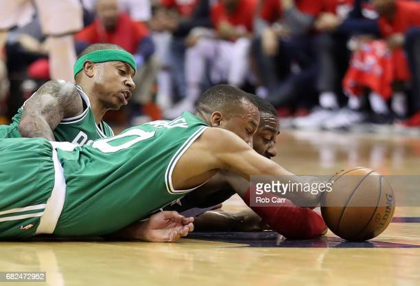 Avery Bradley and Isaiah Thomas of the Boston Celtics dive for a loose ball against John Wall of the Washington Wizards during Game Six of the NBA...