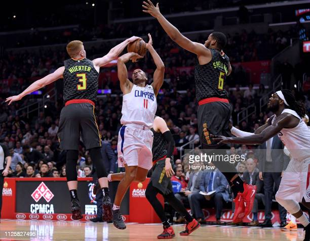 Avery Bradley of the LA Clippers has his shot blocked by Kevin Huerter of the Atlanta Hawks with Omari Spellman during a 123118 Hawks win at Staples...