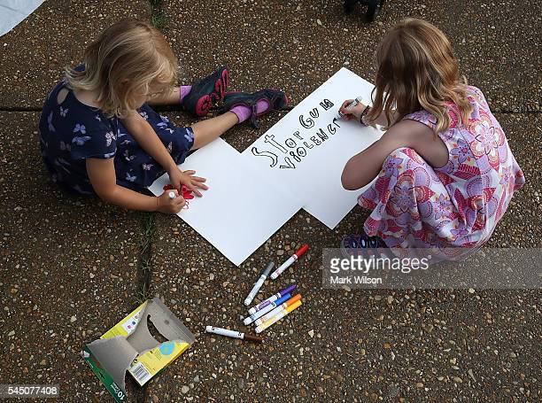 Avery Drobnyk and her sister Eleanor Drobnyk make antigun posters before marching with their mom to Capitol Hill July 5 2016 in Washington DC The...